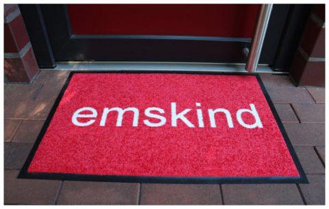 """Rote Fußmatte mit weißem Schriftzug """"emskind"""""""